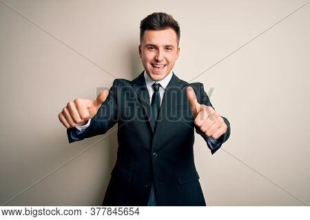 Young handsome business man wearing elegant suit and tie over isolated background approving doing positive gesture with hand, thumbs up smiling and happy for success. Winner gesture.