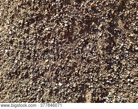 Small Gravel Of Warm Color. The Texture Of The Small Fraction Of The Road Stone. Used For Constructi