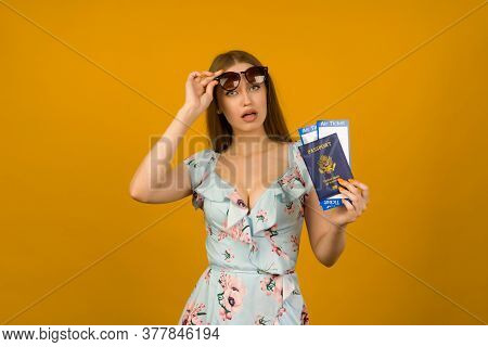 Pop-eyed Young Woman In Blue Dress With Flowers And Sunglasses Is Holding Airline Tickets With A Pas