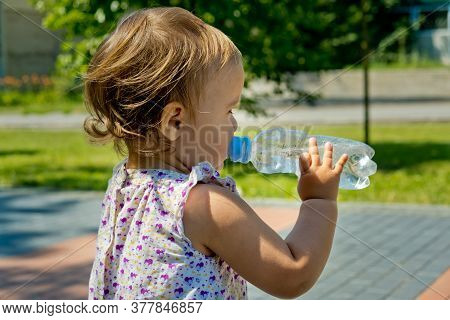 Little Girl Drinks Water From A Bottle. Side View. Close-up.