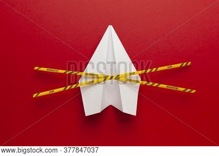 Paper Airplane On Red Background Under Quarantine. Cancellation Of Flights Of Civil And Touristic Av