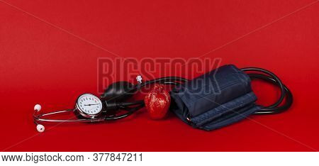 Heart And Mechanical Blood Pressure Monitor On Red Background. Measurement And Control Of Blood Pres