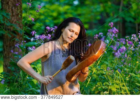 Female Shaman Playing On Shaman Frame Drum At Dawn In The Forest On Background With Leaves And Flowe
