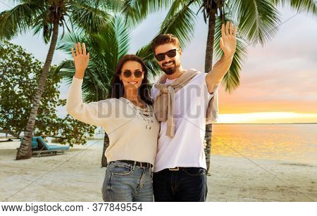 travel, tourism and vacation concept - happy couple waving hands over tropical beach background in french polynesia