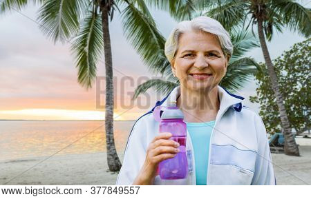fitness, sport and healthy lifestyle concept - happy smiling sporty senior woman with bottle of water over tropical beach background in french polynesia