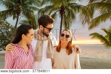 friendship, leisure and people concept - group of happy friends over tropical beach background in french polynesia