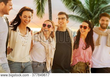 travel, tourism and vacation concept - group of happy friends walking over tropical beach background in french polynesia