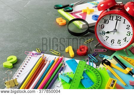 Back To School And Education Concept With Red Alarm Clock And Colorful School Supplies On Blackboard