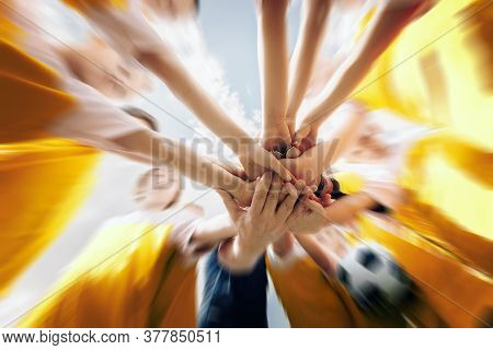 Low Angle Shot Of A Group Of Sports Team Forming A Huddle With Their Hands. Sports Team Stacking Han