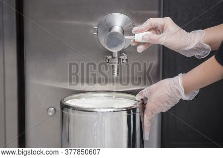 Close-up Of The Hand Of A Worker Who Fills Fresh Milk From A Milk Tank - Preparing Milk For Ice Crea