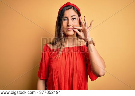 Young beautiful woman colorful summer style over yellow isolated background mouth and lips shut as zip with fingers. Secret and silent, taboo talking
