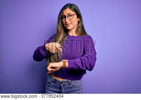 Young beautiful smart woman wearing glasses over purple isolated background In hurry pointing to watch time, impatience, upset and angry for deadline delay