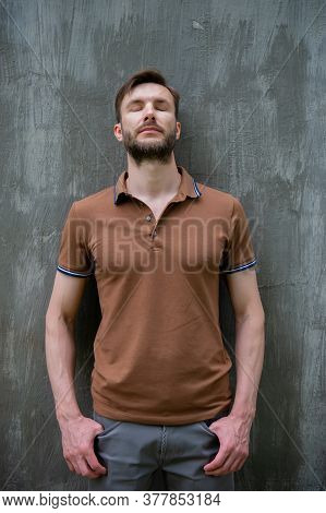 Handsome Bearded Man Stands Against The Wall With His Eyes Closed. Summer Season In The Park.