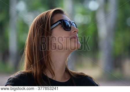 Pretty Girl With Loose Hair In Sunglasses Looks Around. Summer Season In The Park.