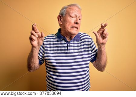 Grey haired senior man wearing casual navy striped t-shirt standing over yellow background gesturing finger crossed smiling with hope and eyes closed. Luck and superstitious concept.
