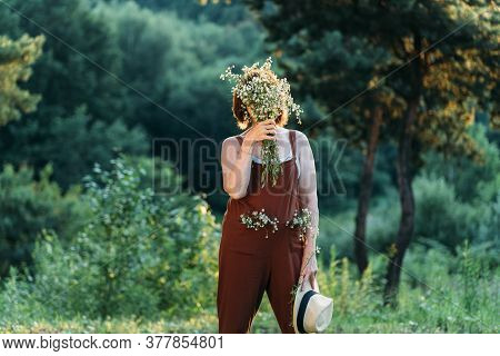 Mature Aged Woman Hiding Eye With Bouquet Of Wild Daisies. In Brown Overalls And Wicker Hat. Hot Sun