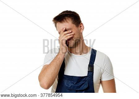 Sad Caucasian Worker Repairman In Blue Overalls Isolated On White Studio Background.