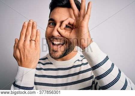 Handsome man with beard showing alliance ring marriage on finger over white background with happy face smiling doing ok sign with hand on eye looking through fingers