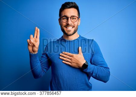 Young handsome man with beard wearing casual sweater and glasses over blue background smiling swearing with hand on chest and fingers up, making a loyalty promise oath