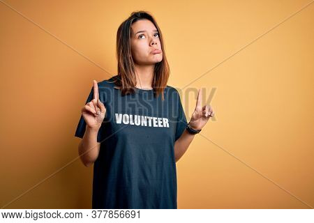 Young beautiful brunette girl doing volunteering wearing t-shirt with volunteer message word Pointing up looking sad and upset, indicating direction with fingers, unhappy and depressed.