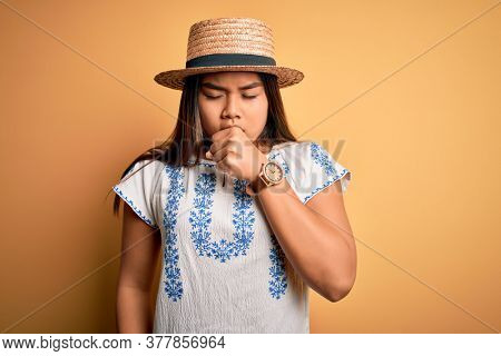 Young beautiful asian girl wearing casual t-shirt and hat standing over yellow background feeling unwell and coughing as symptom for cold or bronchitis. Health care concept.
