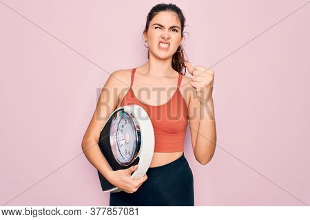 Young beautiful fitness woman wearing sport clothes holding weighting machine scale annoyed and frustrated shouting with anger, crazy and yelling with raised hand, anger concept