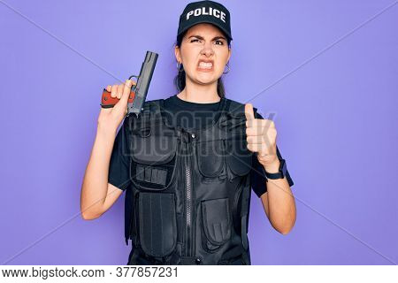 Young police woman wearing security bulletproof vest uniform and holding gun annoyed and frustrated shouting with anger, crazy and yelling with raised hand, anger concept