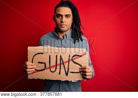 Young african american man with dreadlocks holding banner doing prohibited guns protest with a confident expression on smart face thinking serious
