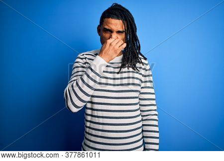 Young handsome african american afro man with dreadlocks wearing casual striped sweater smelling something stinky and disgusting, intolerable smell, holding breath with fingers on nose. Bad smell