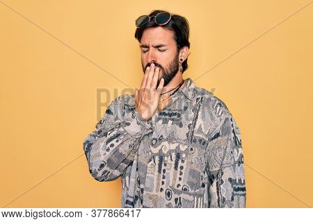 Young handsome hispanic bohemian man wearing hippie style and sunglasses bored yawning tired covering mouth with hand. Restless and sleepiness.