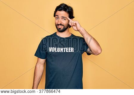 Young handsome hispanic volunteer man wearing volunteering t-shirt as social care Smiling pointing to head with one finger, great idea or thought, good memory
