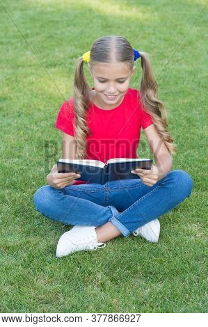 I Love To Read. Happy Reader Summer Outdoors. Little Child Read Book On Green Grass. Summer Reading