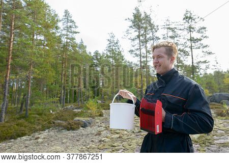 Portrait Of Happy Young Handsome Man Thinking While Holding Bucket And Berry Picker In The Forest