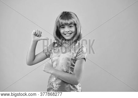 Asian Girl Pointing Finger. Small Chinese Girl In Purple Wig. Happy Kid In Traditional Chinese Gown.