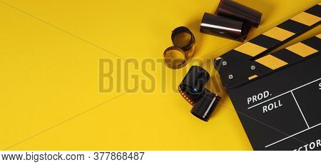 Clapper Board Or Movie Slate With Black&yellow Color And Film Roll On Yellow Background. It Is Used