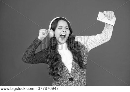 Music Is Voice Of Soul. Happy Girl Enjoy Music Red Background. Little Child Wear Headphones Playing