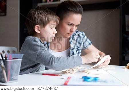 Mom Helps Her Son Make A Wooden Toy From A Construction Set. Woman And Her Child, Leisure