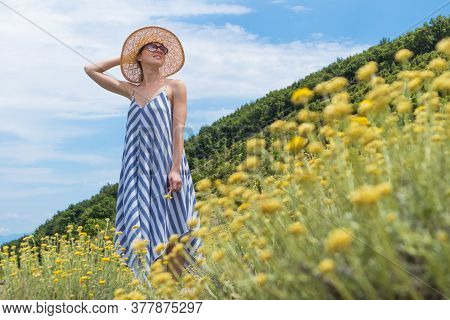 Young Woman Wearing Striped Summer Dress And Straw Hat Standing In Super Bloom Of Wildflowers, Relax