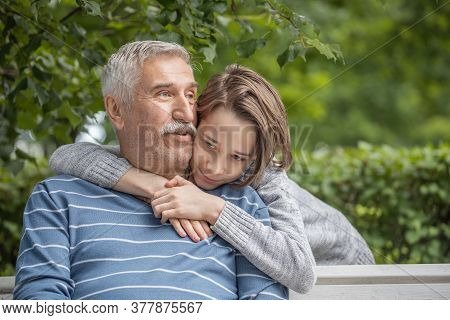 Portrait Of Grandson And Grandfather, Teenager Boy Hugs His Grandfather In The Park On A Bench, Summ