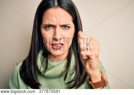Young brunette woman with blue eyes wearing turtleneck sweater over white background annoyed and frustrated shouting with anger, crazy and yelling with raised hand, anger concept