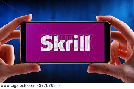 Hands Holding Smartphone Displaying Logo Of Skrill