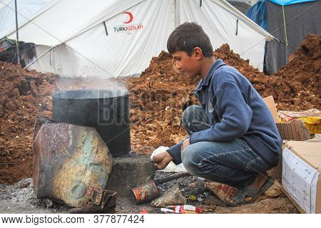 Aleppo, Syria, 20 December 2019 A Refugee Child In The Camp Cooks Food On Firewood Outdoors.