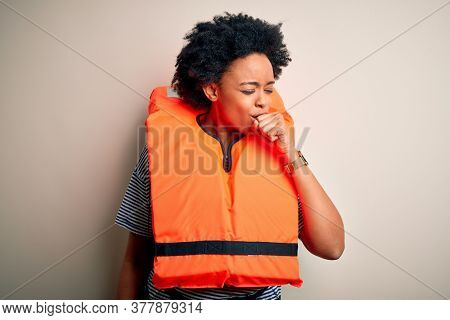 Young African American afro woman with curly hair wearing orange protection lifejacket feeling unwell and coughing as symptom for cold or bronchitis. Health care concept.