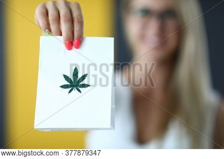 Female Hand Holds Paper Bag With An Image Of Marijuana Symbol Closeup. Online Delivery Of Marijuana