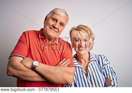 Senior beautiful couple standing together over isolated white background happy face smiling with crossed arms looking at the camera. Positive person.