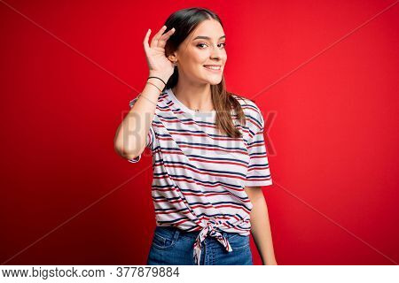 Young beautiful brunette woman wearing casual striped t-shirt standing over red background smiling with hand over ear listening an hearing to rumor or gossip. Deafness concept.