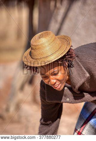 african woman wearing a het in her yard in a village in botswana