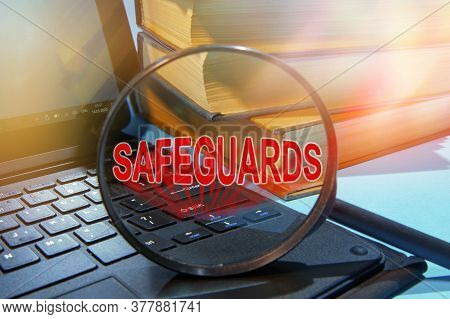 Laptop Computer And Book With A Magnifying Glass. Text Safeguards On Magnifying Glass