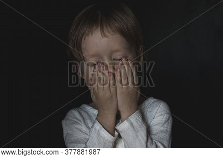 Portrait Of A Scared Little Boy Child. The Kid Covered His Mouth With His Hands, Closed His Eyes. Th
