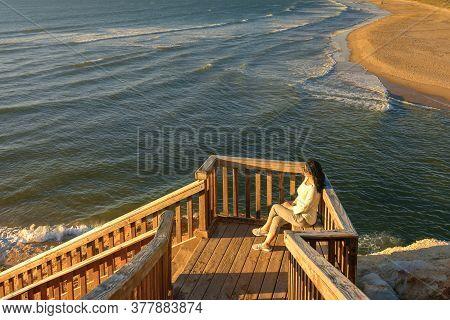 Woman Sitting On Iconic Port Noarlunga Boardwalk While Watching Beautiful  Sunset, South Australia